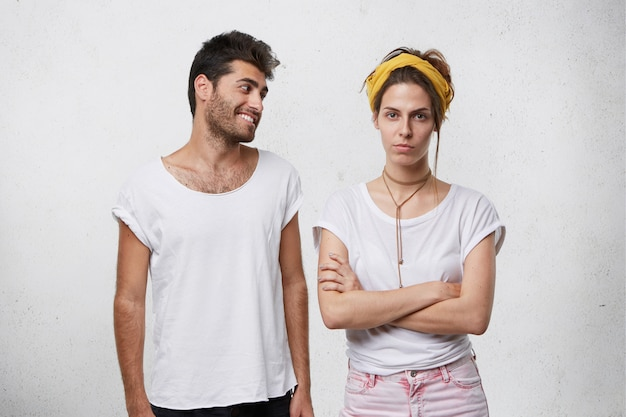 Handsome positive bearded male in white t-shirt trying to convince or apologize to his angry upset girlfriend in yellow headband who is looking offended, keeping her arms crossed
