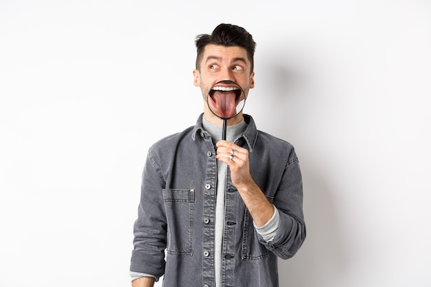 Handsome positive guy showing white perfect teeth and tongue with magnifying glass, looking left at logo, standing against white background.