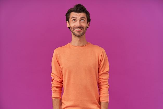ブルネットの髪と剛毛を持つハンサムで前向きな男。袖をまくり上げたオレンジ色のセーターを着ています