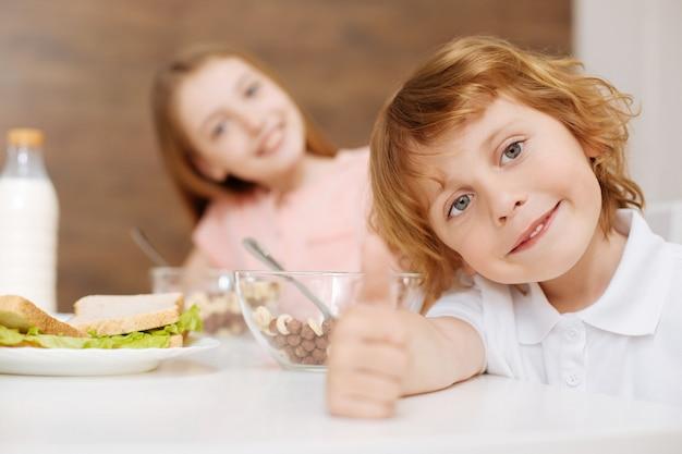 그의 형제와 함께 테이블에 앉아 하루의 첫 번째 식사를 먹고 즐기는 잘 생긴 긍정적 인 좋은 아이