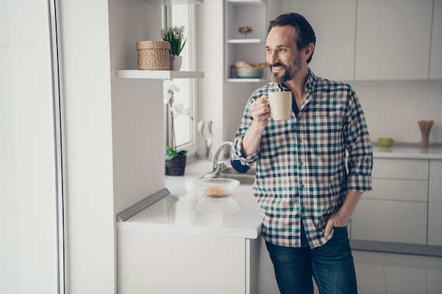 キッチンに立っている落ち葉で窓を見て手に新鮮なカカオのカップを保持しているハンサムな前向きな楽観的な素敵な嬉しい男