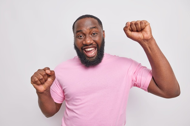 Un bell'uomo con la barba lunga positivo fa ballare il trionfo alza i pugni si diverte alla festa esprime emozioni felici sorrisi indossa una maglietta rosa casual isolata sul muro grigio