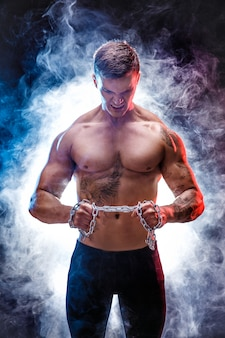 Handsome power athletic man bodybuilder doing exercises with chain, tearing. fitness muscular body on dark background. perfect male. awesome bodybuilder, tattoo, posing.