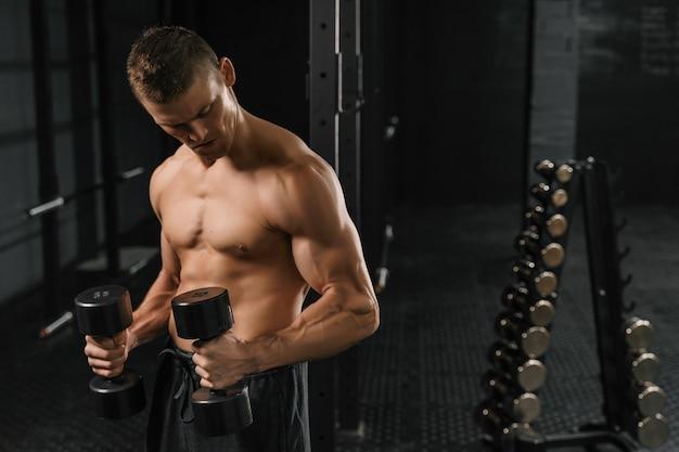 ジムでダンベルを使ってエクササイズをしているハンサムなパワーアスリート男性ボディービルダー。暗い背景のフィットネス筋肉ボディ。 crossfitトレーニング