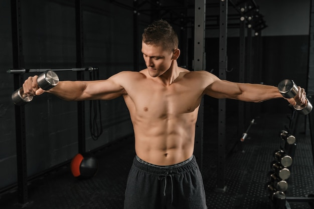 Спортивная (ый) человек культурист красавец делает упражнения с гантелями