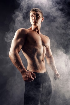 Handsome power athletic man bodybuilder. fitness muscular body on dark smoke background. perfect male. awesome bodybuilder, tattoo, posing.