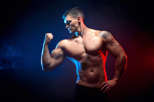 ハンサムなパワー運動男ボディービルダー。暗い煙の背景にフィットネス筋肉ボディ。完璧な男性。素晴らしいボディービルダー、タトゥー、ポーズ。