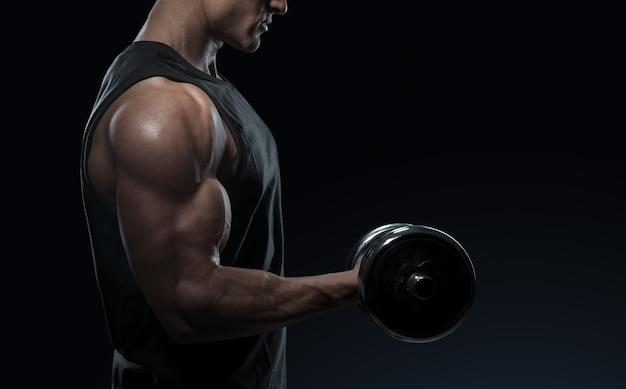 아령으로 근육을 펌핑하는 훈련에 잘 생긴 파워 운동 남자. 완벽한 삼각근, 어깨, 이두근, 삼두근 및 가슴을 갖춘 강력한 보디빌더입니다. 파워 피트니스 남자의 클로즈업입니다.