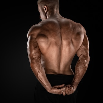 Handsome power athletic man showing his back strong bodybuilder with shoulders biceps triceps and chest