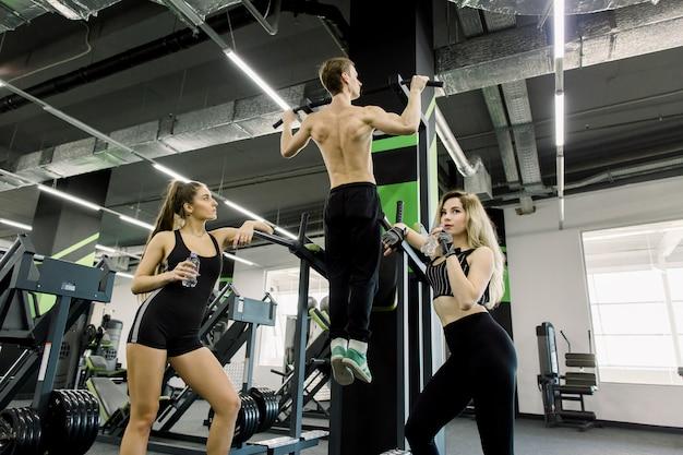Тренировка человека красивой силы атлетическая накачивая вверх мышцы спины тянет вверх в спортзале. сильный культурист тренируется в спортзале, тренирует спину. две девушки с бутылками с водой стоят возле бара