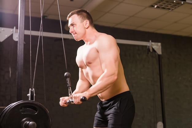 Handsome power athletic man training pumping up muscles with sport equipment.