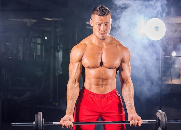自信を持って楽しみにしているバーベルを持つハンサムなパワーアスリート男。 6パック、完璧な腹筋、肩、上腕二頭筋、上腕三頭筋、胸を備えた強力なボディービルダー