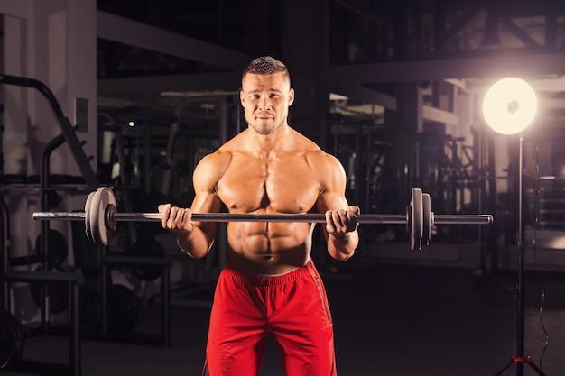 バーベルを持つハンサムなパワーアスリート男。 6パック、完璧な腹筋、肩を持つ強力なボディービルダー