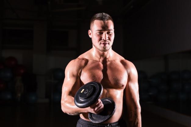 自信を持って楽しみにしているダンベルを持つハンサムなパワーアスリート男。 6パック、完璧な腹筋、肩、上腕二頭筋、上腕三頭筋、胸を備えた強力なボディービルダー