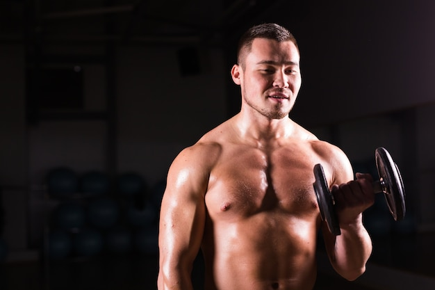 Handsome power athletic man with dumbbell. strong bodybuilder with six pack, perfect abs, shoulders