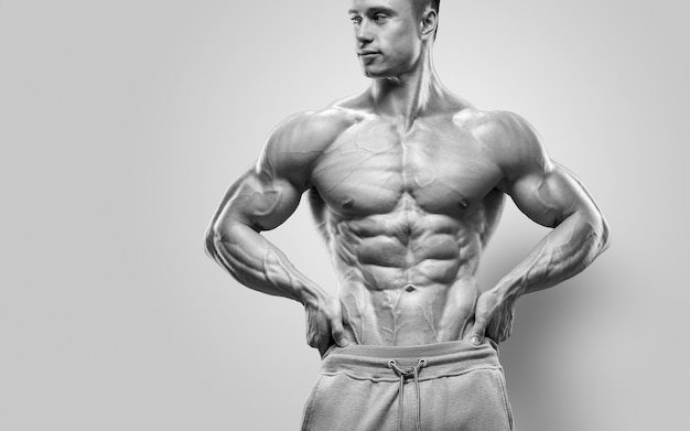 Handsome power athletic young man with great physique strong bodybuilder with six pack perfect abs s...