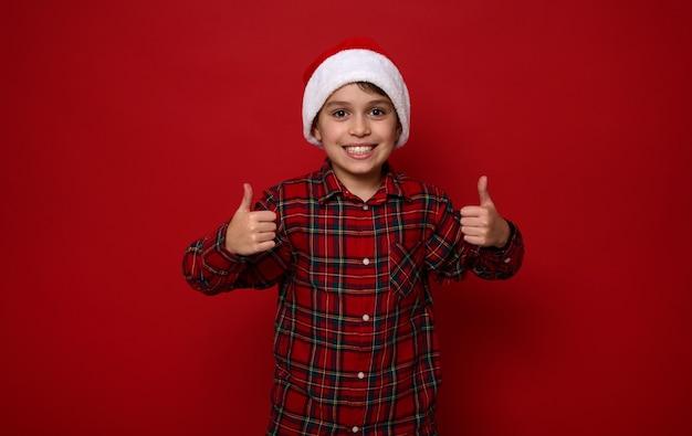 Красивый малолетний мальчик в красной клетчатой рубашке в шляпе санта-клауса улыбается зубастой улыбкой и показывает большие пальцы вверх, глядя в камеру, позирует на цветном фоне с копией пространства для рождественской рекламы