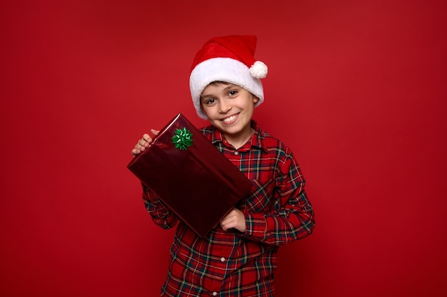 Красивый малолетний мальчик в шляпе санта-клауса и красной клетчатой рубашке позирует на цветном фоне с рождественским подарком, улыбнулся красивой зубастой улыбкой, глядя в камеру. скопируйте место для рекламы