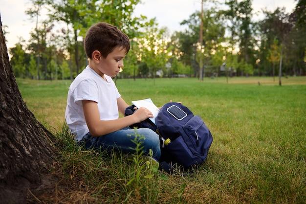 ハンサムな思春期前の男子生徒がバックパックからワークブックを取り出し、都市公園の緑の芝生に座って、屋外で宿題をする準備ができています。野外で学校の仕事をしている愛らしい子供