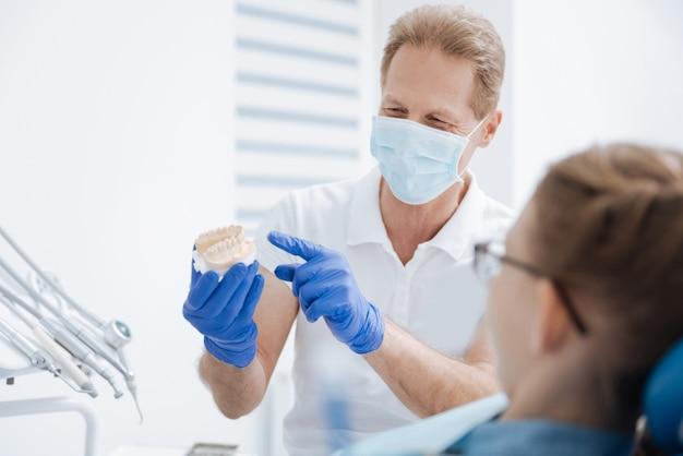 어린 소녀가 건강하기 위해 치아를 치료해야하는 방법을 설명하는 잘 생긴 정확한 훈련 된 의사