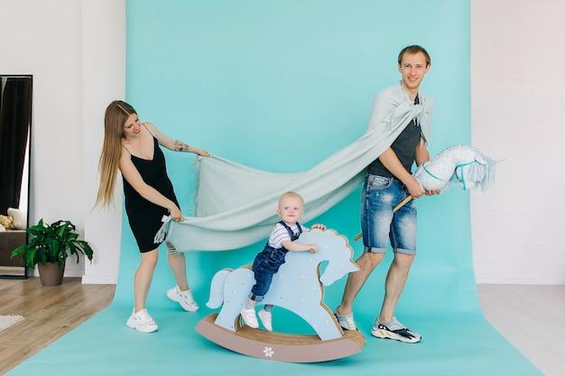ハンサムな王子と幼い息子を持つシックな王女、おもちゃの馬の王子と格子縞のレインコート