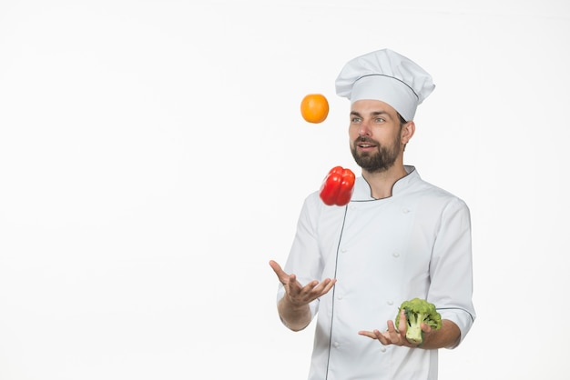 Handsome professional chef in uniform juggling with vegetables on white background