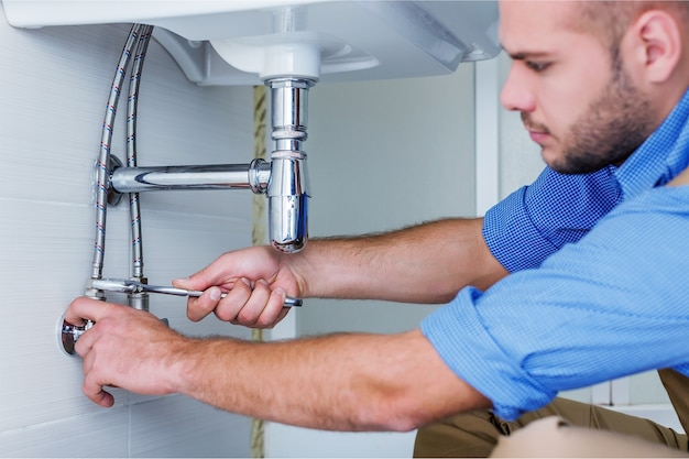 ハンサムなプロの配管工固定パイプ。配管修理サービス。