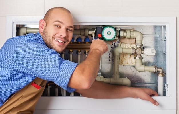 Handsome professional plumber fixing pipes. plumbing repair service.