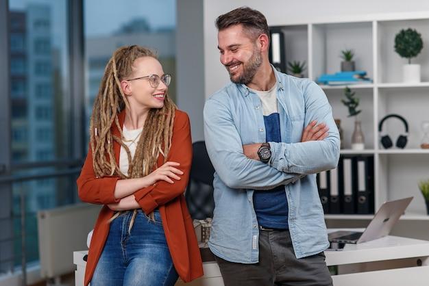 Красивые профессиональные улыбающиеся коллеги архитектора стоят спиной к спине в студии современного дизайна.