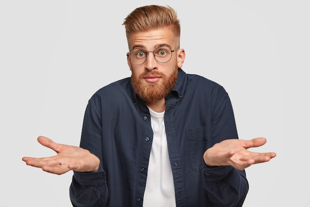 Handsome puzzled young ginger man with clueless expression, feels doubt, makes choice between two things, wears round spectacles, has foxy hair and beard, expresses hesitation