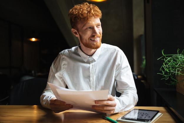 Handsome readhead bearded man sitting at wooden table, holding papers while looking aside