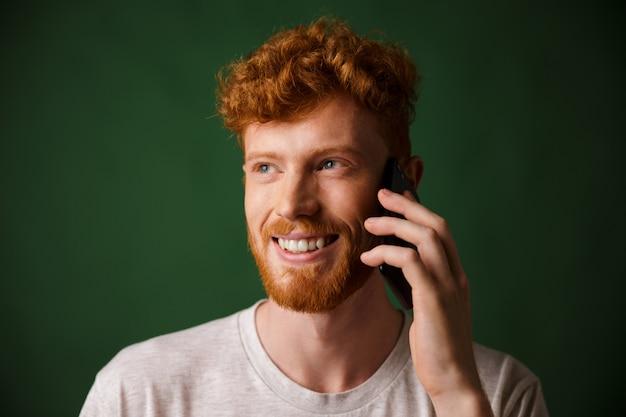 Handsome redhead bearded man talking on phone