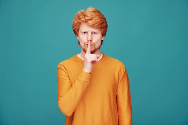 落ち着きを保つように頼みながら口の近くで指を保持しているオレンジ色のセーターのハンサムな赤毛の男