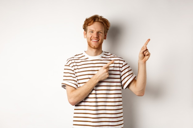 Handsome redhead man showing logo, pointing fingers right and smiling, standing over white background.
