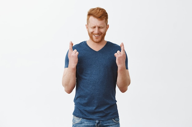 Handsome redhead man wishing for luck. crossing fingers while standing over gray wall with closed eyes and hopeful smile, praying for fulfillment of desire, wearing casual blue t-shirt