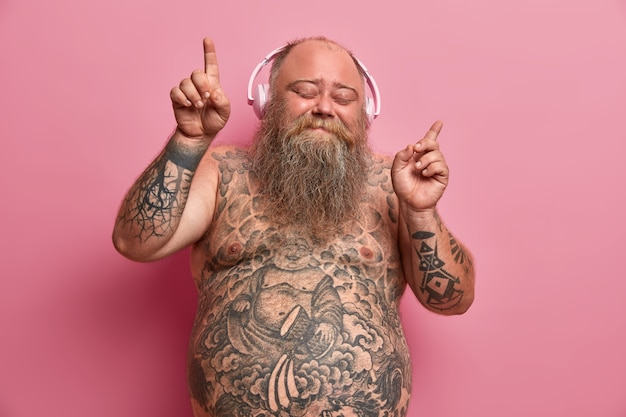 Handsome relaxed obese overweight man dances to music in headphones, enjoys every bit of song, raises hands and points with fingers, stands with eyes closed, whole body covered with tattoos.