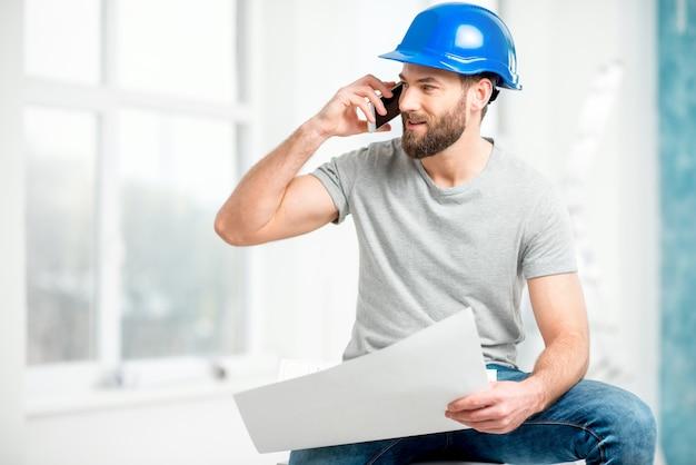 白いインテリアの図面と電話で話しているヘルメットのハンサムな修理工またはビルダー