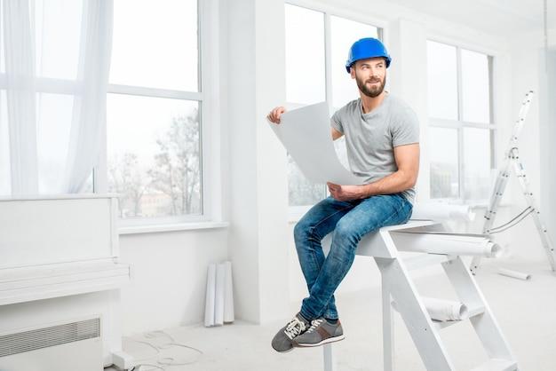 Красивый ремонтник или строитель в каске, работая с чертежами по ремонту интерьера квартиры