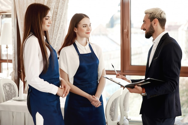 ハンサムなレストランマネージャーは、作業プロセスについてウェイトレスに話しています。