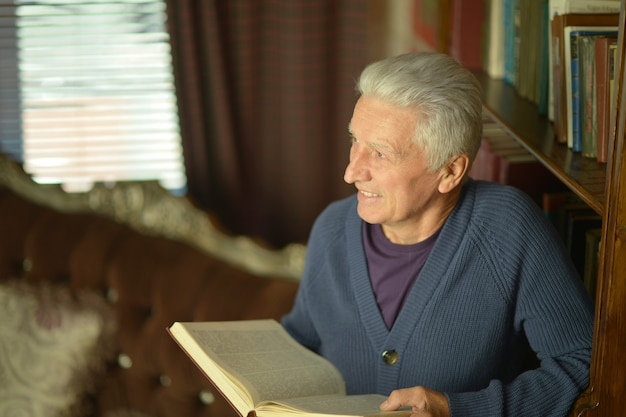 Handsome retired man reading booktrait of handsome retired man reading book