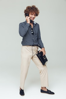 Handsome retro man holding telephone in hands.