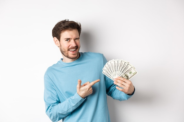 Handsome rich guy winking at camera, showing income, pointing finger at earned money and smiling, standing over white background.