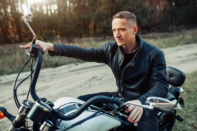 Handsome rider guy in black biker jacket on classic style cafe racer motorcycle at sunset