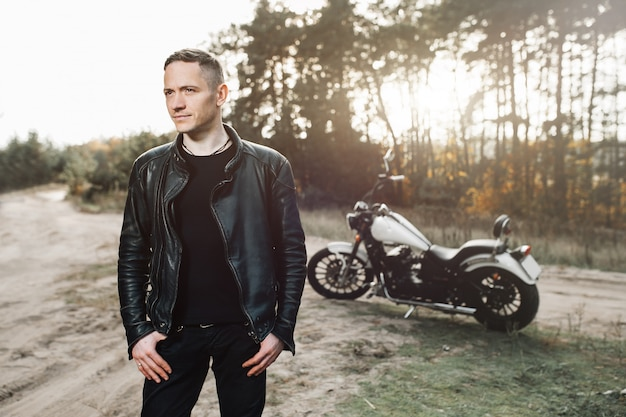 Handsome rider guy in black biker jacket on classic style cafe racer motorcycle at sunset.