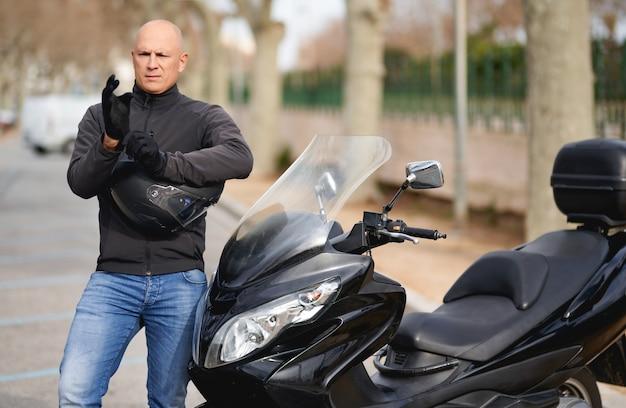ハンサムなライダーガイレーサーオートバイ。バイカーはオートバイの手袋を着用します。