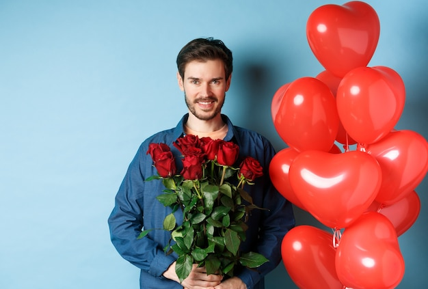 빨간 장미를 들고 웃 고, 파란색 배경 위에 하트 풍선 근처에 서 잘 생긴 로맨틱 남자.