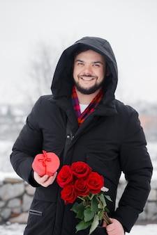 손에 빨간 장미 부케와 잘 생긴 로맨틱 젊은 남자