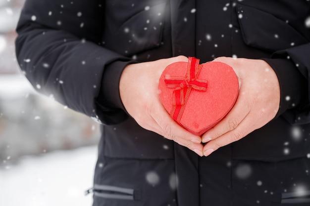 붉은 심장 모양의 상자와 잘 생긴 로맨틱 젊은 남자