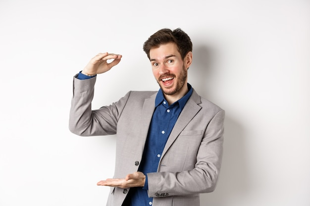 Handsome salesman in suit showing big size, large income, smiling at camera enthusiastic, standing on white background.