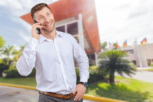 Handsome salesman talking on mobile phone